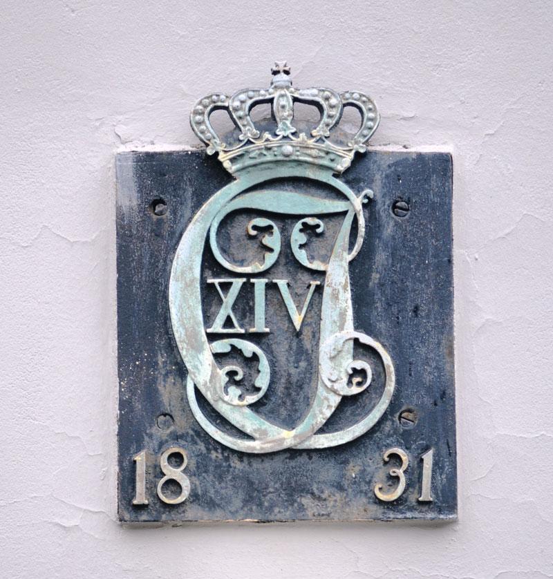 Karl XIV Johans monogram på trappehuset i bakgården til Billington jernvareforretning – opprinnelig «Kronprins Carl Augusts lærde Skole». Foto: Svein Norheim.
