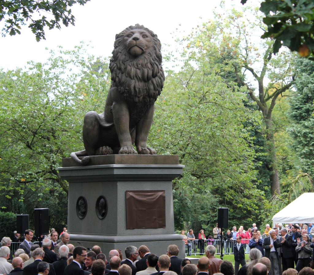 """Etter nesten 150 års reise kunne """"Isted-løven"""" igjen avdukes på kirkegården i Flensburg sommeren 2011. På sokkelen sees medaljongene av Helgesen og Schleppegrell. Nede til venstre skimtes den danske prins Joachim, som sto for avdukingen. Foto: Soenke Rahn."""
