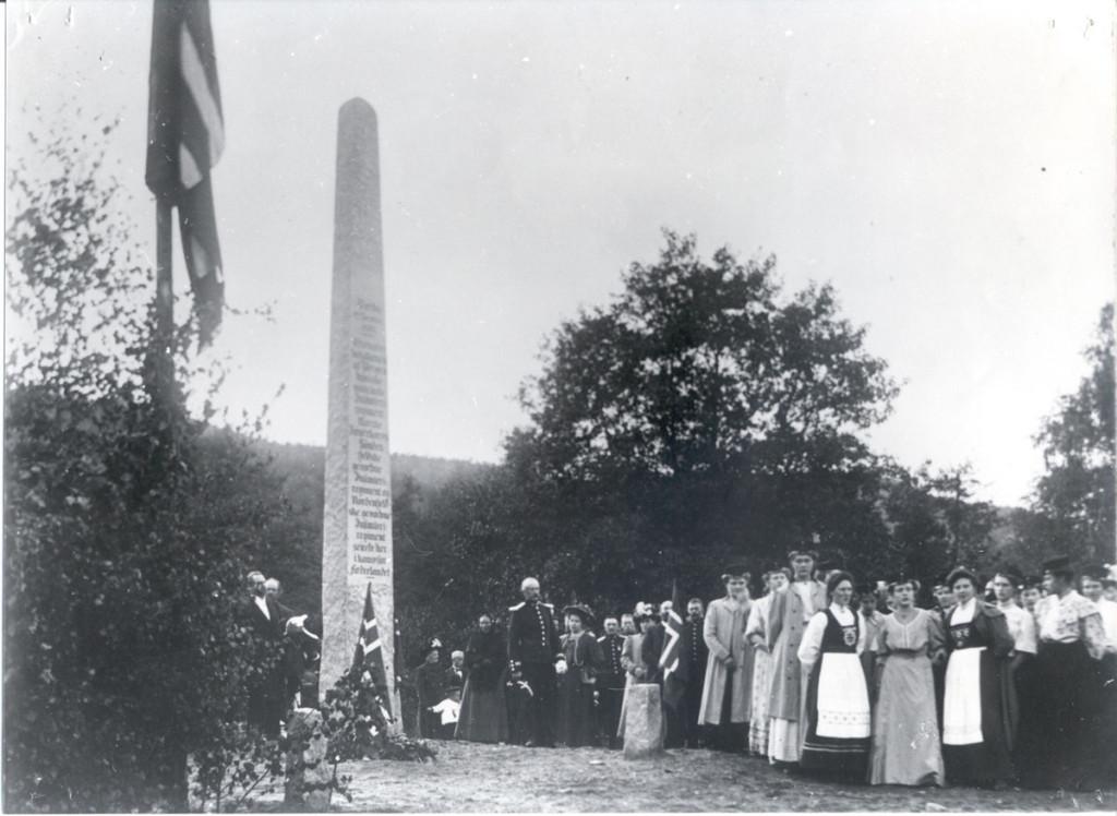 Postkort fra avdukingen av bautastenen på Berby 12. september 1908. Det var ikke bare menn med fine titler til stede. Foran ser vi festkledte kvinner hvorav noen i bunad. Halden historiske Samlinger.